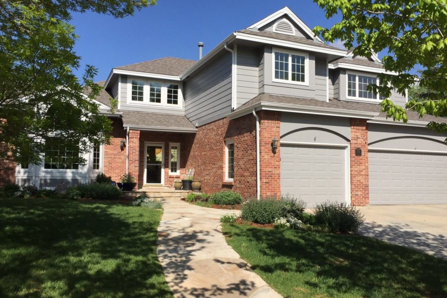 Light grey house with red brick garage