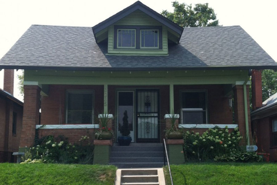 Brick house with green columns and front porch
