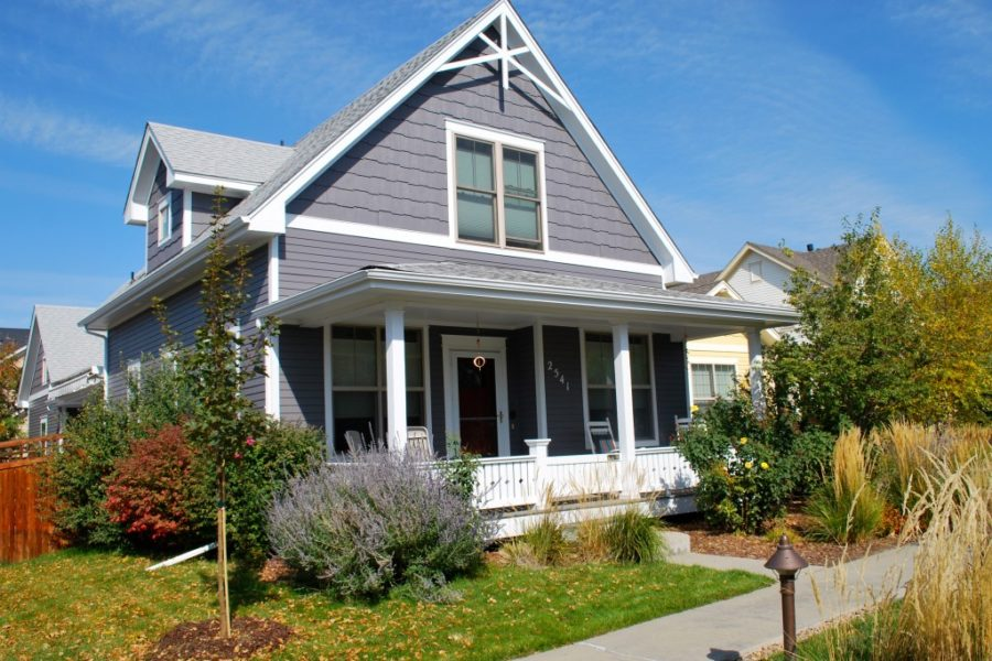 Dark grey house with white accents and front porch